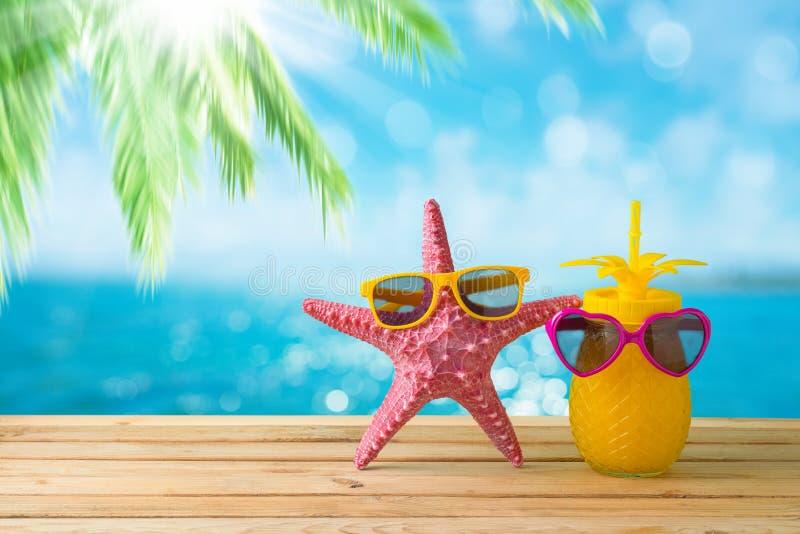 Conceito das f?rias de ver?o com suco bonito da estrela do mar e de abacaxi com os ?culos de sol sobre o fundo da praia do mar imagem de stock royalty free