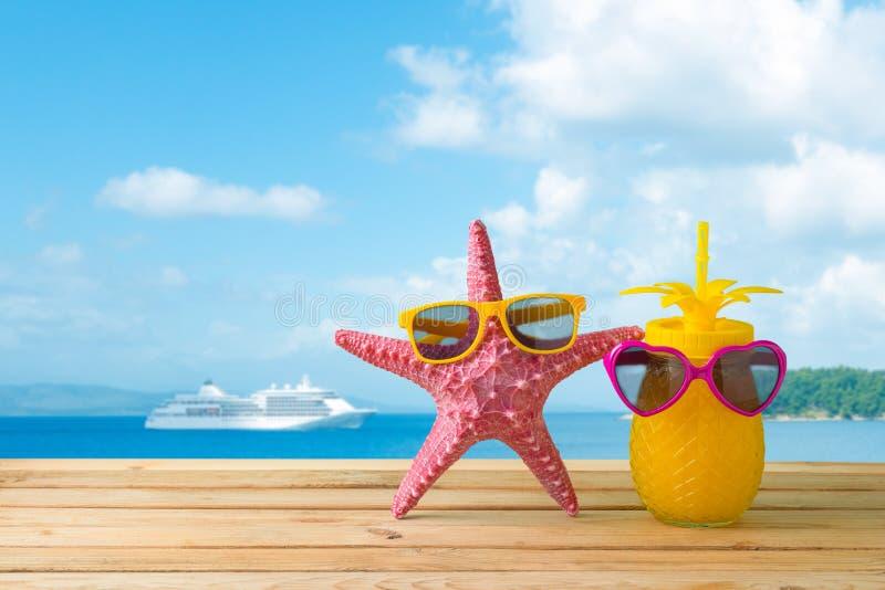 Conceito das f?rias de ver?o com suco bonito da estrela do mar e de abacaxi com os ?culos de sol sobre o fundo da praia do mar fotografia de stock