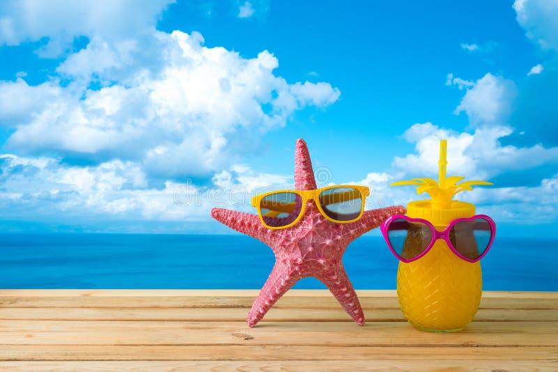 Conceito das f?rias de ver?o com suco bonito da estrela do mar e de abacaxi com os ?culos de sol sobre o fundo da praia do mar fotos de stock