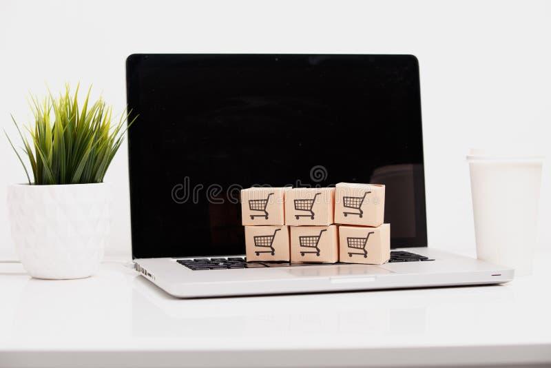 Conceito de compra em linha do serviço do comércio eletrónico e de entrega: Caixas de papel com um logotipo do carrinho de compra imagens de stock royalty free