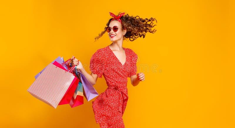 Conceito de compras da compra e vendas da mo?a feliz com pacotes no fundo amarelo foto de stock royalty free