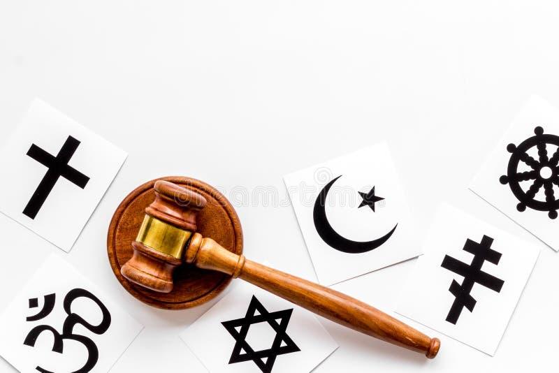 Conceito de conflito religioso Símbolos das religiões do mundo perto de gavel em fundo branco, espaço de cópia superior foto de stock royalty free
