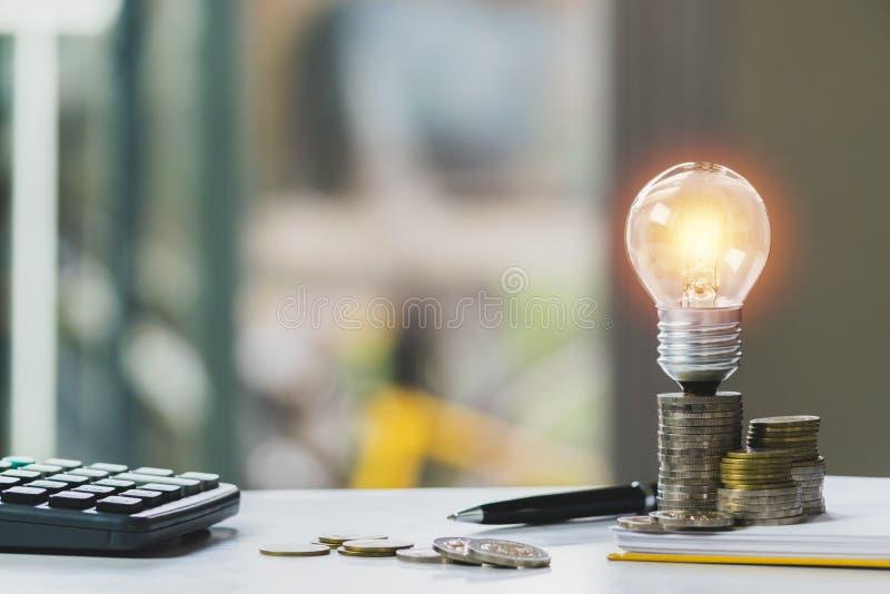 Conceito de contabilidade com moedas, a ampola e a calculadora na tabela foto de stock royalty free