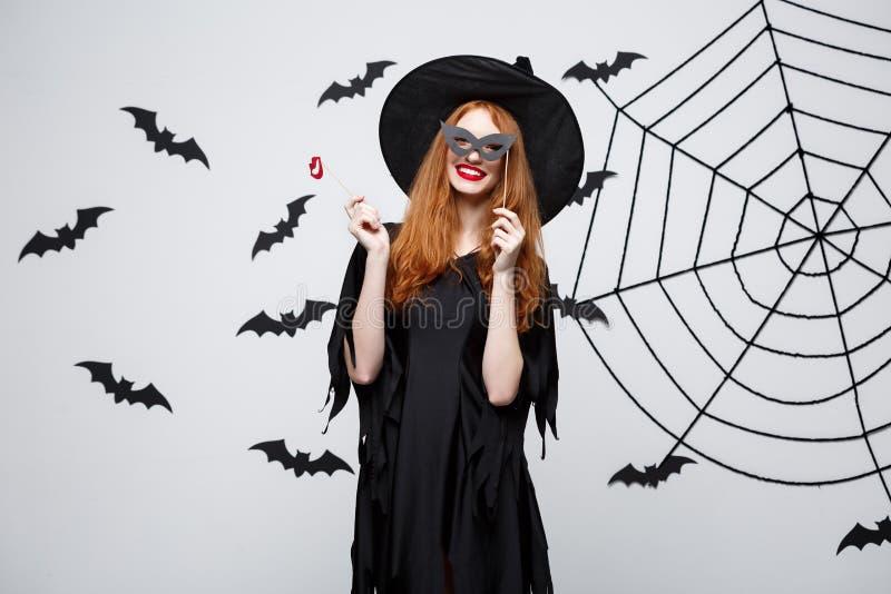 Conceito de Dia das Bruxas - as meninas bonitas na bruxa preta vestem guardar suportes do partido fotos de stock royalty free