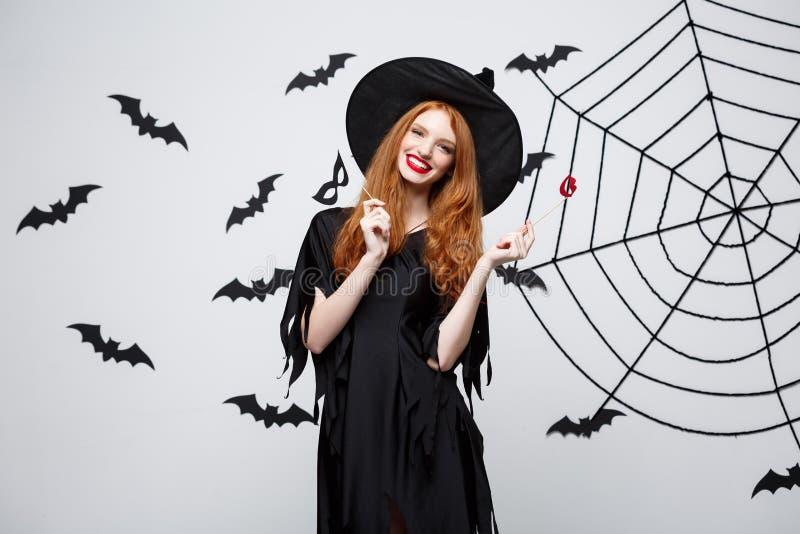 Conceito de Dia das Bruxas - as meninas bonitas na bruxa preta vestem guardar suportes do partido fotos de stock