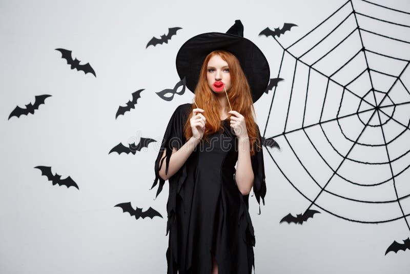 Conceito de Dia das Bruxas - as meninas bonitas na bruxa preta vestem guardar suportes do partido imagem de stock