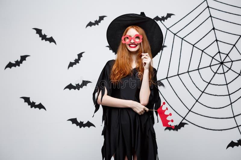 Conceito de Dia das Bruxas - as meninas bonitas na bruxa preta vestem guardar suportes do partido imagens de stock