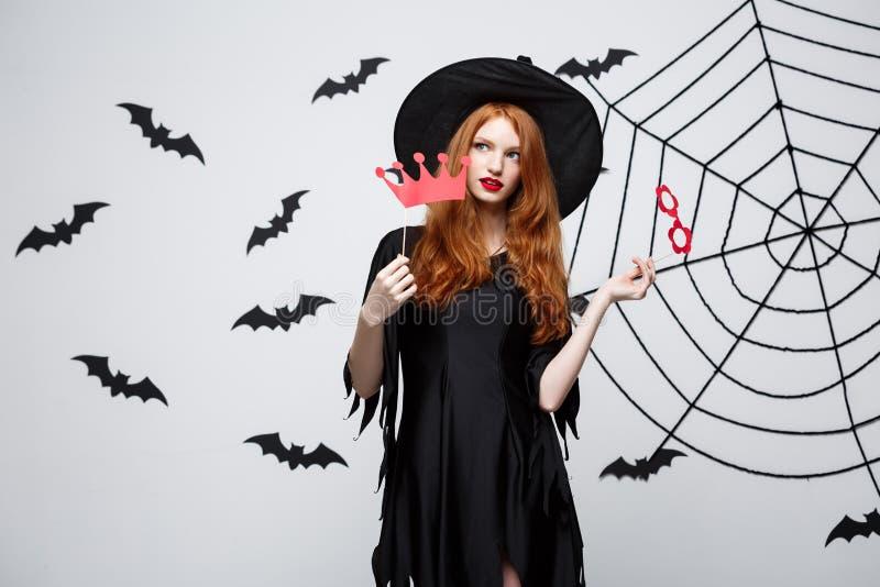 Conceito de Dia das Bruxas - as meninas bonitas na bruxa preta vestem guardar suportes do partido fotografia de stock