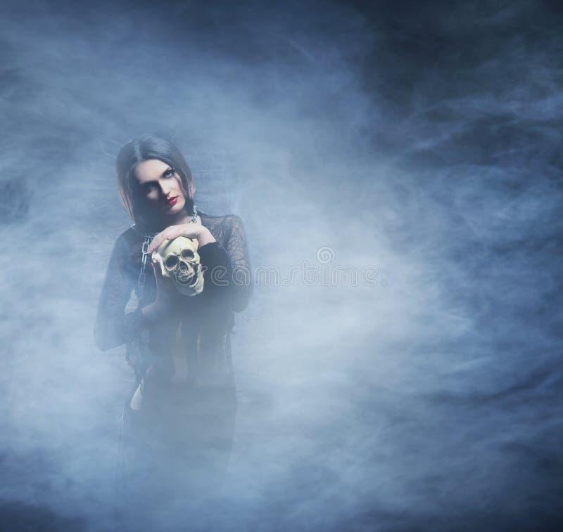 Conceito de Dia das Bruxas: a bruxa nova e 'sexy' faz a feitiçaria fotografia de stock royalty free