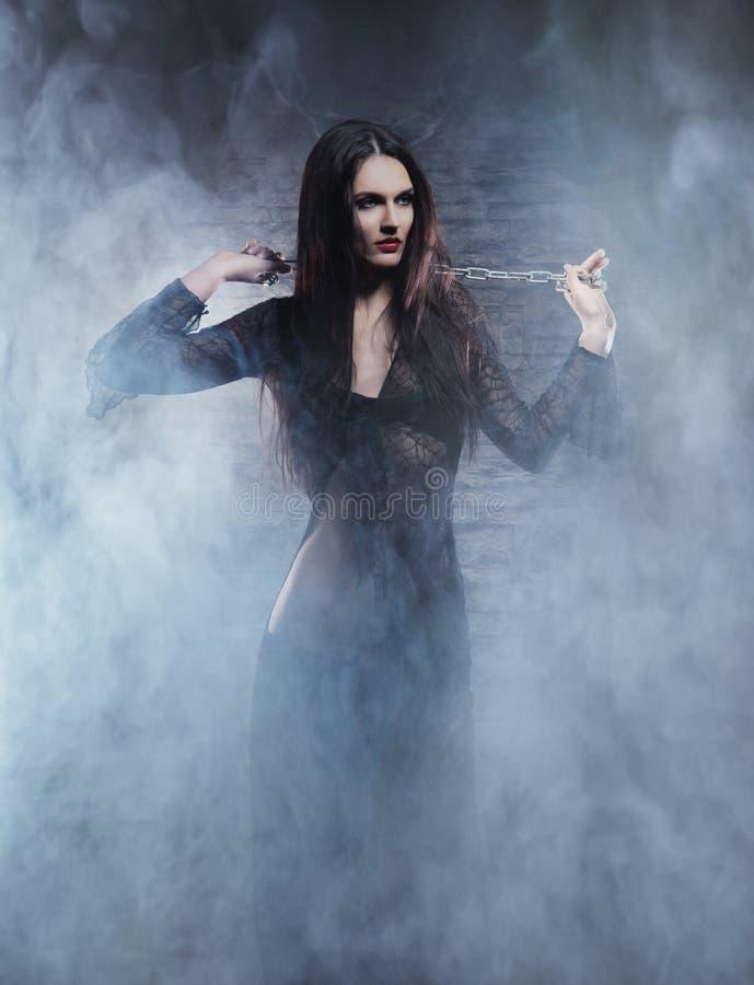 Conceito de Dia das Bruxas: bruxa nova e 'sexy' no Dungeon imagem de stock