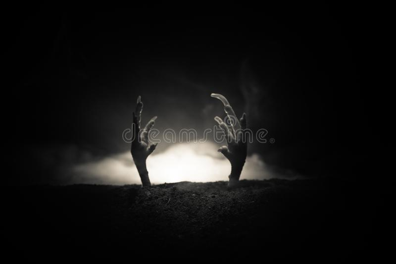 Conceito de Dia das Bruxas, mão do zombi que aumentam para fora da terra ou mão do zombi que sai de sua sepultura imagem de stock