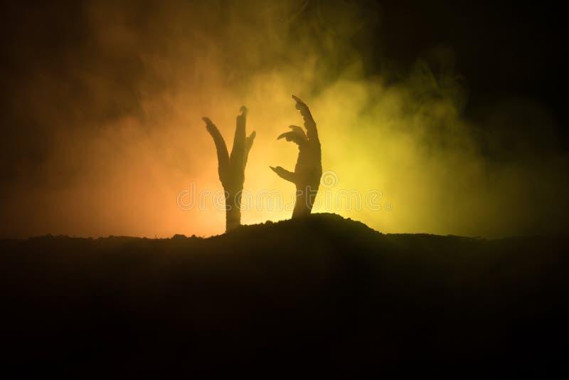 Conceito de Dia das Bruxas, mão do zombi que aumentam para fora da terra ou mão do zombi que sai de sua sepultura foto de stock