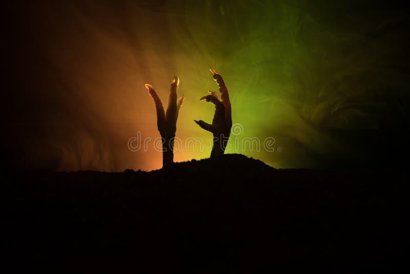 Conceito de Dia das Bruxas, mão do zombi que aumentam para fora da terra ou mão do zombi que sai de sua sepultura fotografia de stock royalty free