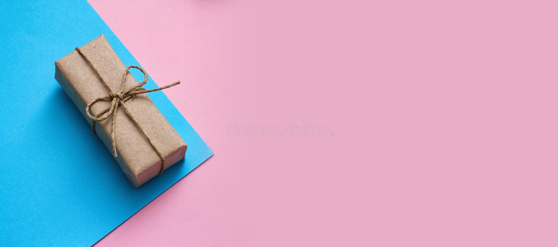 Conceito de dia de determinação do gênero Caixa de doação embrulhada em papel artesanal e fio de cânhamo Fundo rosa e azul Menina foto de stock royalty free