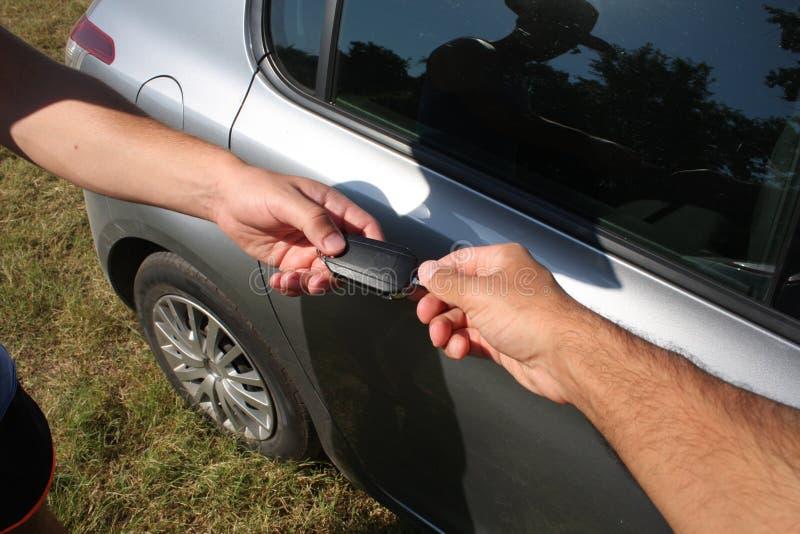 Conceito de dois homens de negócios ao vender um carro em uma exposição automóvel, c fotografia de stock royalty free