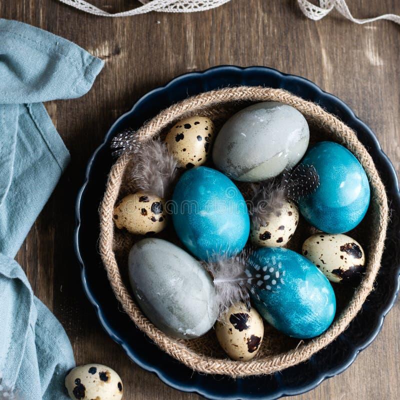 Conceito de easter da mola, - ovos da páscoa naturalmente tingidos, ovos de codorniz, penas, bolo de easter, fundo de madeira es imagens de stock