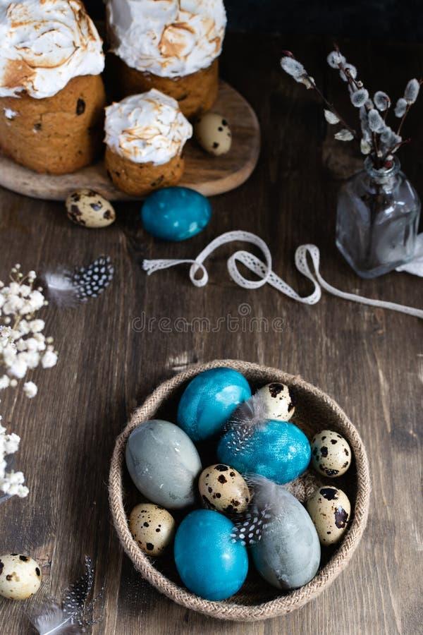 Conceito de easter da mola, - ovos da páscoa naturalmente tingidos, ovos de codorniz, penas, bolo de easter, fundo de madeira es foto de stock royalty free