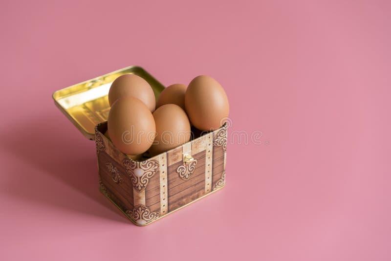 Conceito de Easter ovos em uma caixa em um fundo cor-de-rosa Copie o espaço ovos da páscoa em uma arca do tesouro foto de stock royalty free
