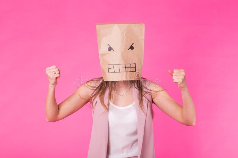 Conceito de emoções negativas - mulher irritada com um saco de papel em sua cara imagem de stock