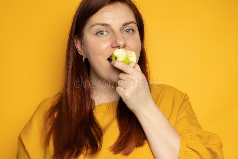 Conceito de equilíbrio nutricional adequado Menina come uma maçã verde, parada sobre um fundo amarelo foto de stock
