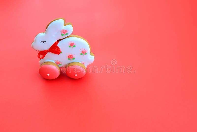 Conceito de férias em Páscoa, biscoitos de pão branco rosa feitos à mão, sob a forma de coelho, em fundo vermelho Pão-pão imagem de stock royalty free