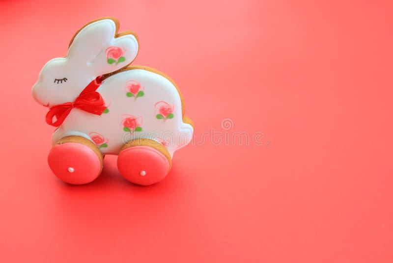 Conceito de férias em Páscoa, biscoitos de pão branco rosa feitos à mão, sob a forma de coelho, em fundo vermelho Pão-pão imagens de stock royalty free