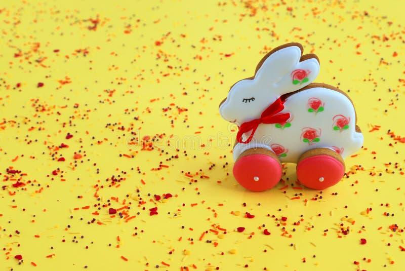 Conceito de férias em Páscoa, biscoitos de pão branco rosa, feitos à mão, sob a forma de coelho, num fundo amarelo Paschal de pão foto de stock