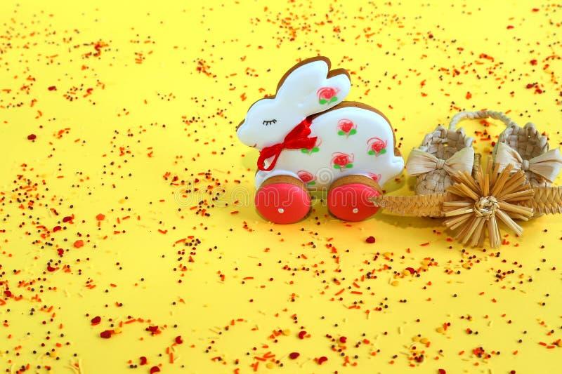 Conceito de férias em Páscoa, biscoitos de pão branco rosa, feitos à mão, sob a forma de coelho, num fundo amarelo Paschal de pão foto de stock royalty free