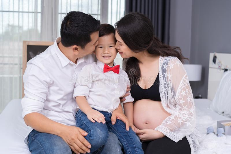 Conceito de família feliz, mãe grávida e pai beijando o menino da criança fotos de stock