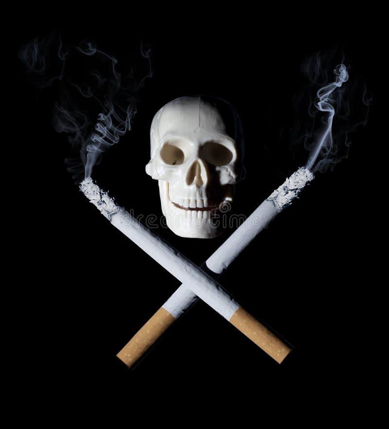 Conceito de fumo parado: Cigarros com crânio fotografia de stock royalty free