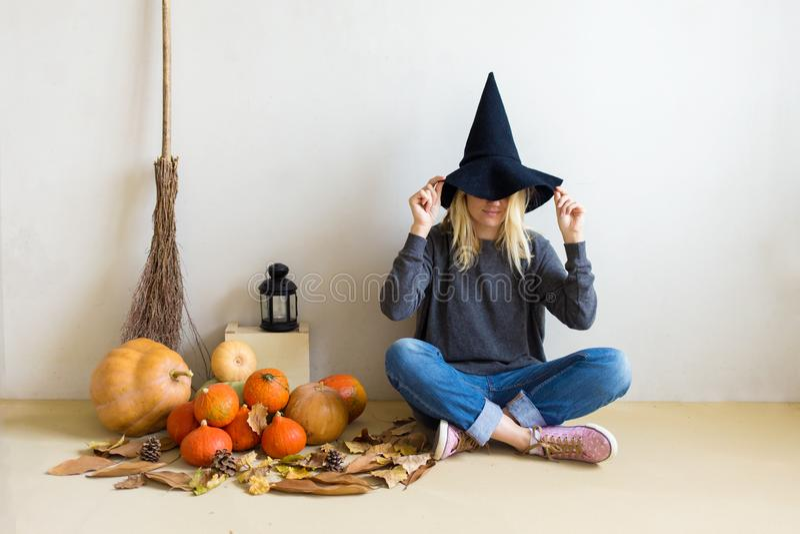 Conceito de Halloween Menina loura bonita em um chapéu da bruxa com abóboras e uma vassoura em um fundo branco imagens de stock royalty free
