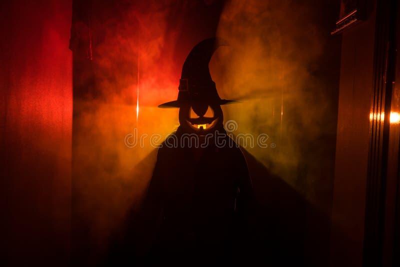 Conceito de Halloween Silhueta assustador no corredor escuro com cabeça da abóbora Luz tonificada com névoa no fundo Foco seletiv fotografia de stock royalty free
