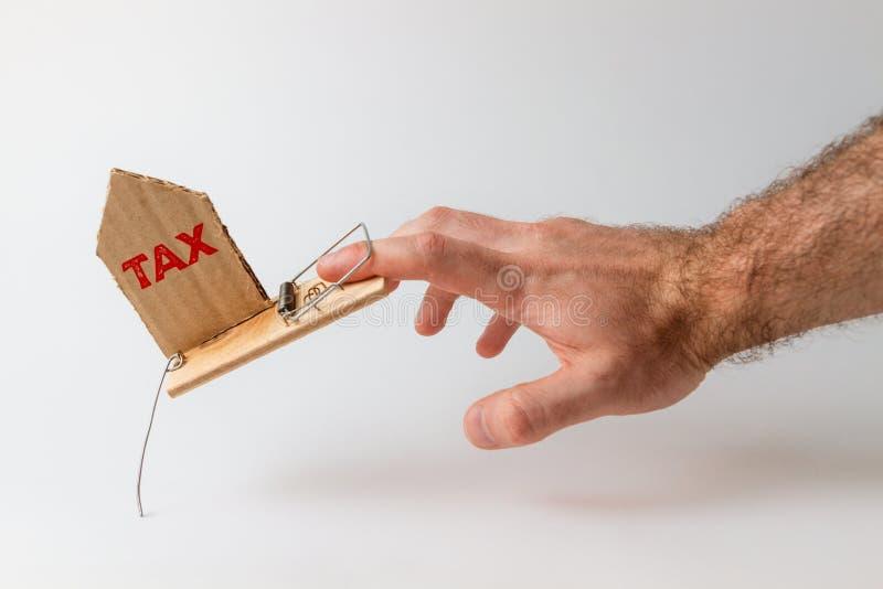 Conceito de investimentos e riscos bancários A mão de um homem cai numa armadilha, com uma inserção de papelão com o texto TAX imagens de stock royalty free