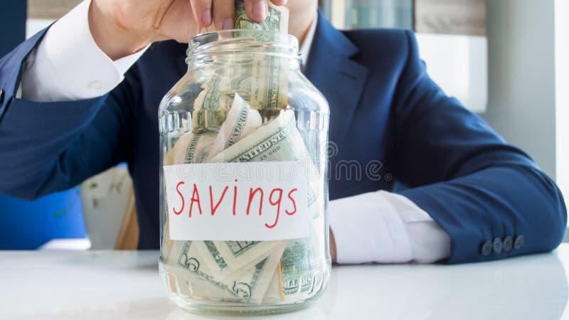 Conceito de investir o dinheiro Homem de negócios novo que põe o dólar no frasco de vidro completamente do dinheiro imagens de stock