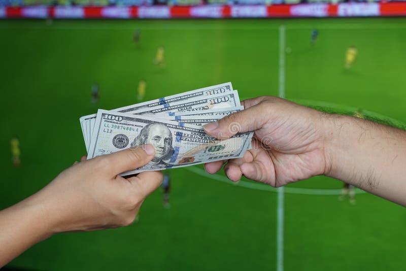 Conceito de jogo do futebol: A mão dá o dinheiro a outro sobre a tevê foto de stock