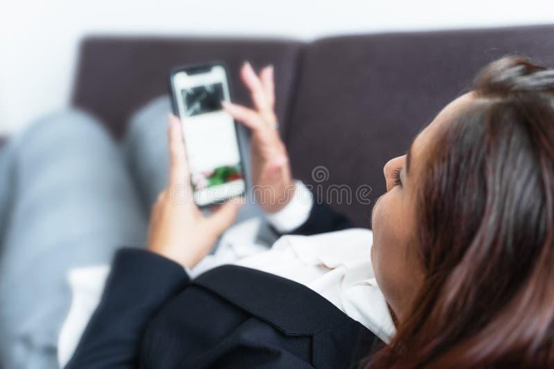 Conceito de mídia social, mulher jovem usa smartphone deitado no sofá, navegando na internet ou escrevendo mensagem imagens de stock