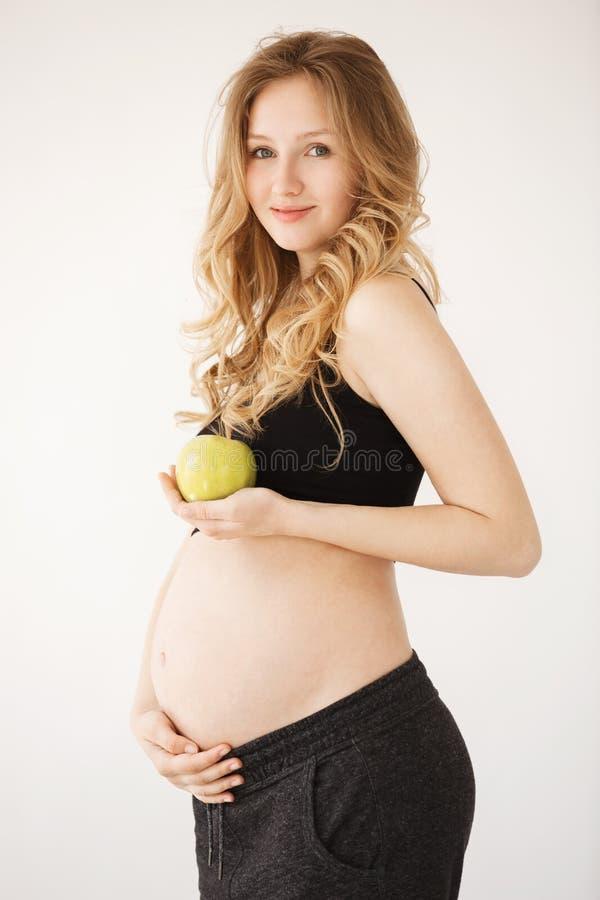 Conceito de maternidade saudável Retrato vertical da mulher gravida europeia nova bonita com cabelo louro no preto confortável imagem de stock royalty free