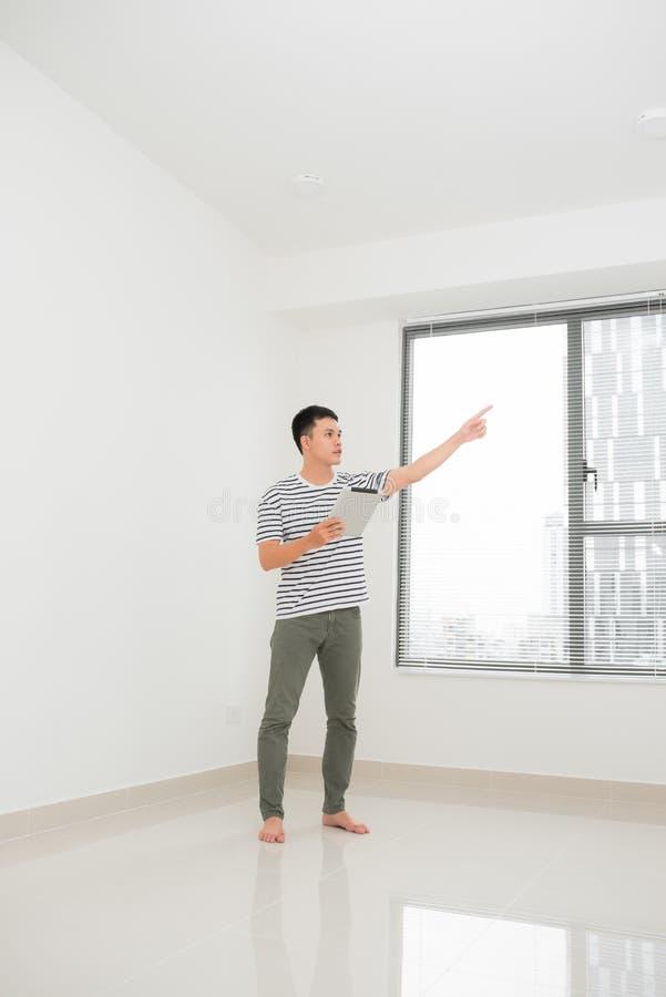 Conceito de mover-se, casa de compra planos do homem novo a reparar e um apartamento do projeto foto de stock