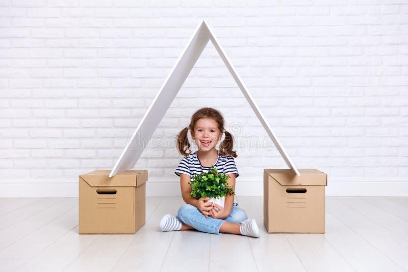 Conceito de mover-se e do abrigar menina feliz da criança com caixas fotografia de stock royalty free