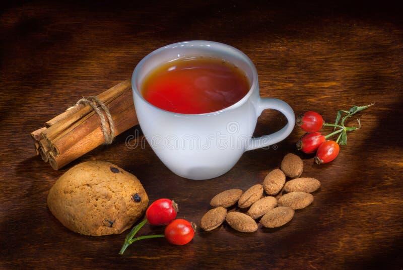 Conceito de Natal com uma xícara de chá quente, biscoitos e decorações num tronco sobre fundo de madeira, foco seletivo imagens de stock