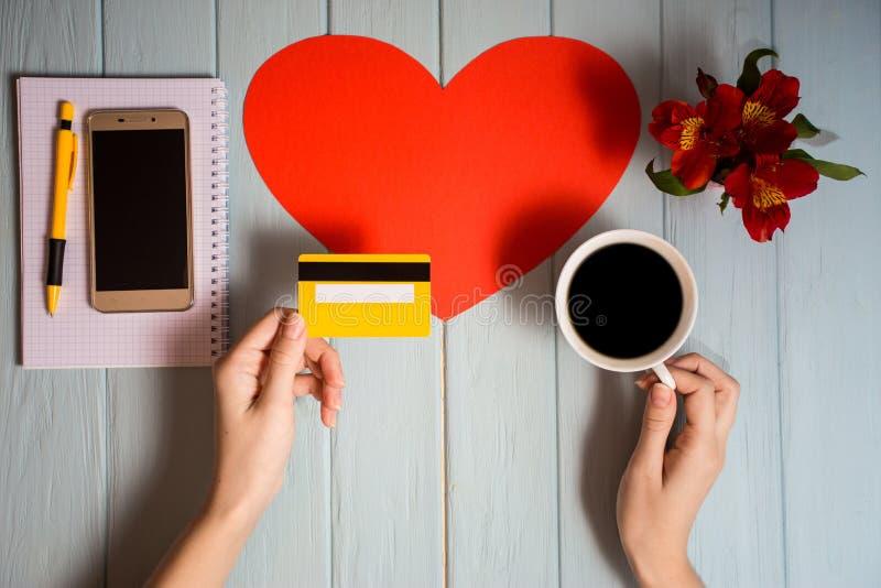Conceito de novas tecnologias em linha, bens de compra da compra compra da mulher com cartão e telefone do débito-crédito no café foto de stock