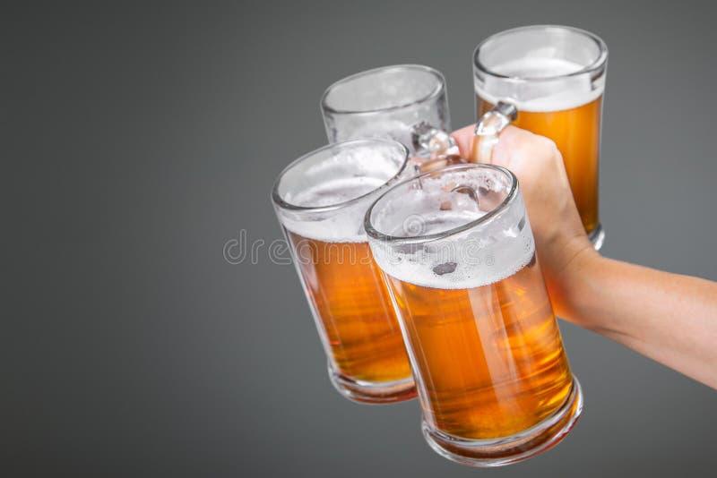 Conceito de Oktoberfest - entregue guardar vidros com cerveja imagens de stock royalty free