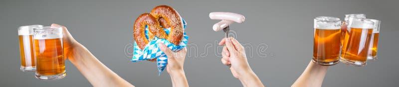 Conceito de Oktoberfest - mãos que guardam a cerveja e o pretzel imagem de stock royalty free