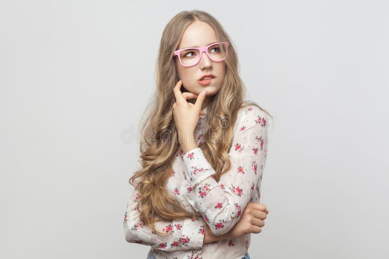 Conceito de pensamento Mulher loura de cabelos compridos da perplexidade em ey cor-de-rosa fotografia de stock