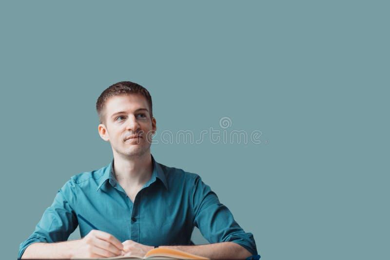 Conceito de pensamento positivo Retrato de um homem de negócios novo que olha ao lado direito e que senta-se na mesa e na escrita fotografia de stock