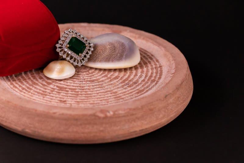 Conceito de presente de aniversário Anéis de esmeralda e caixa de presente vermelha com concha na areia Pedra com fundo preto fotografia de stock royalty free