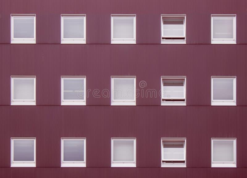 Conceito de projeto exterior: A fileira abstrata da imagem de janelas fechados e abertas decora na parede vermelha da construção fotos de stock royalty free