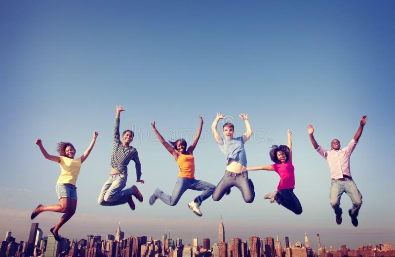 Conceito de salto da cidade da felicidade da amizade dos povos alegres imagem de stock