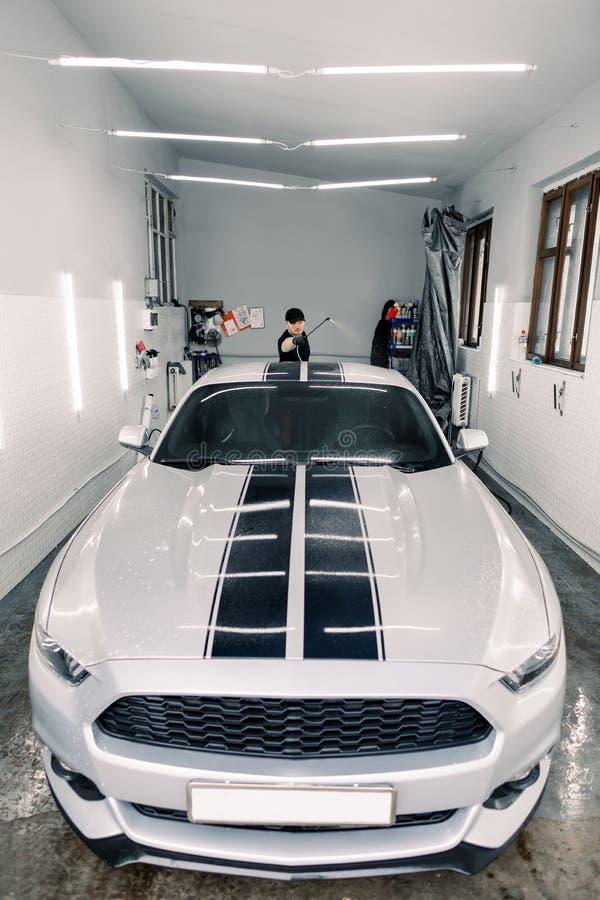 Conceito de serviço automático, lavagem de automóveis e limpeza Um jovem trabalhador caucasiano bonitão em camiseta preta e chapé imagens de stock