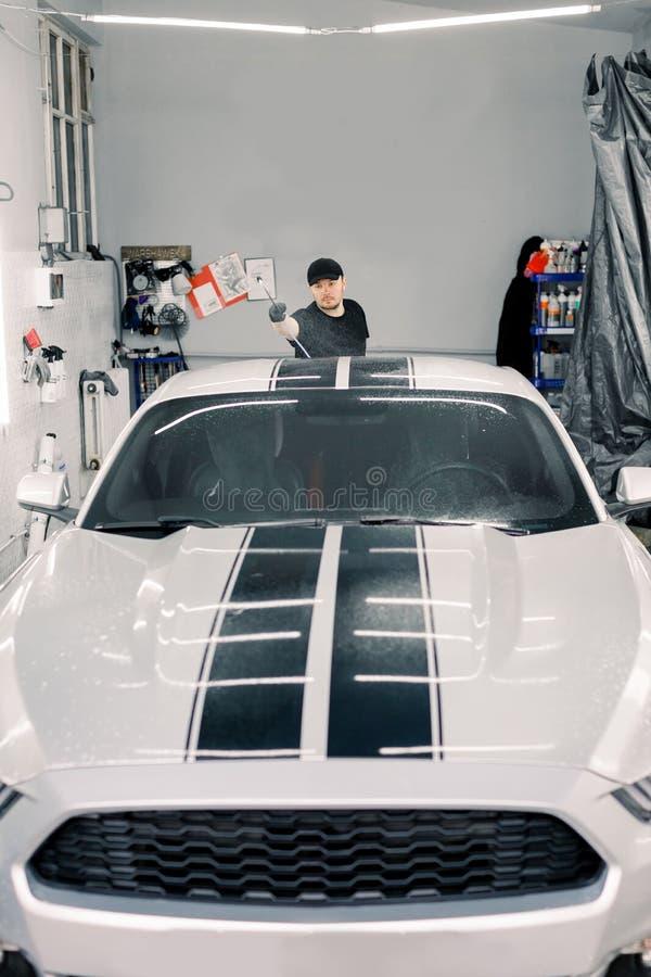 Conceito de serviço automático, lavagem de automóveis e limpeza Um jovem trabalhador caucasiano bonitão em camiseta preta e chapé imagem de stock royalty free